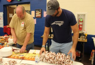 Red Cross volunteer David Kingsbury gets help serving sandwiches to shelter residents from Edgewood Elementary School Principal Jared Worthington