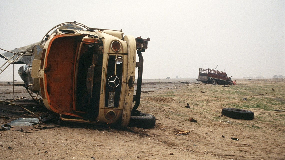 Iraqi transport trucks lie wrecked in the desert north of Kuwait City after Iraqi forces retreated from the area during Operation Desert Storm. (Courtesy of Wikimedia)