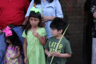 Sophia, Ava and Ramon Hernandez hold the palms they received at St. Jude.