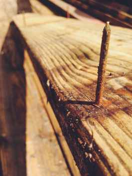 A rusty nail sticking out of some reclaimed lumber