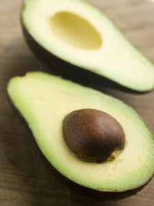 Open face avocado laying on a table with seed in one side