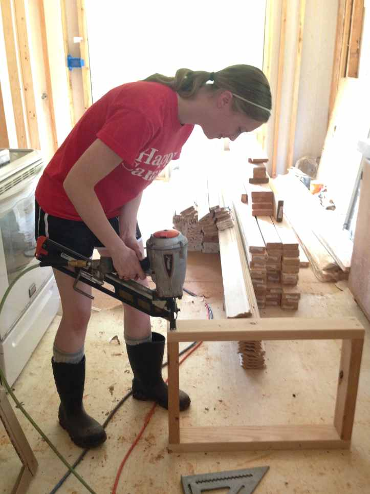Jenn using a framing nail gun to build the box for one of our wall mounted AC units.