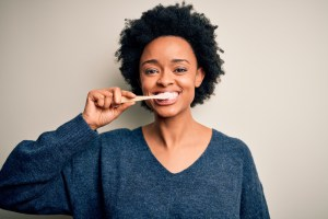 woman brushing her teeth using tooth brush and oral paste