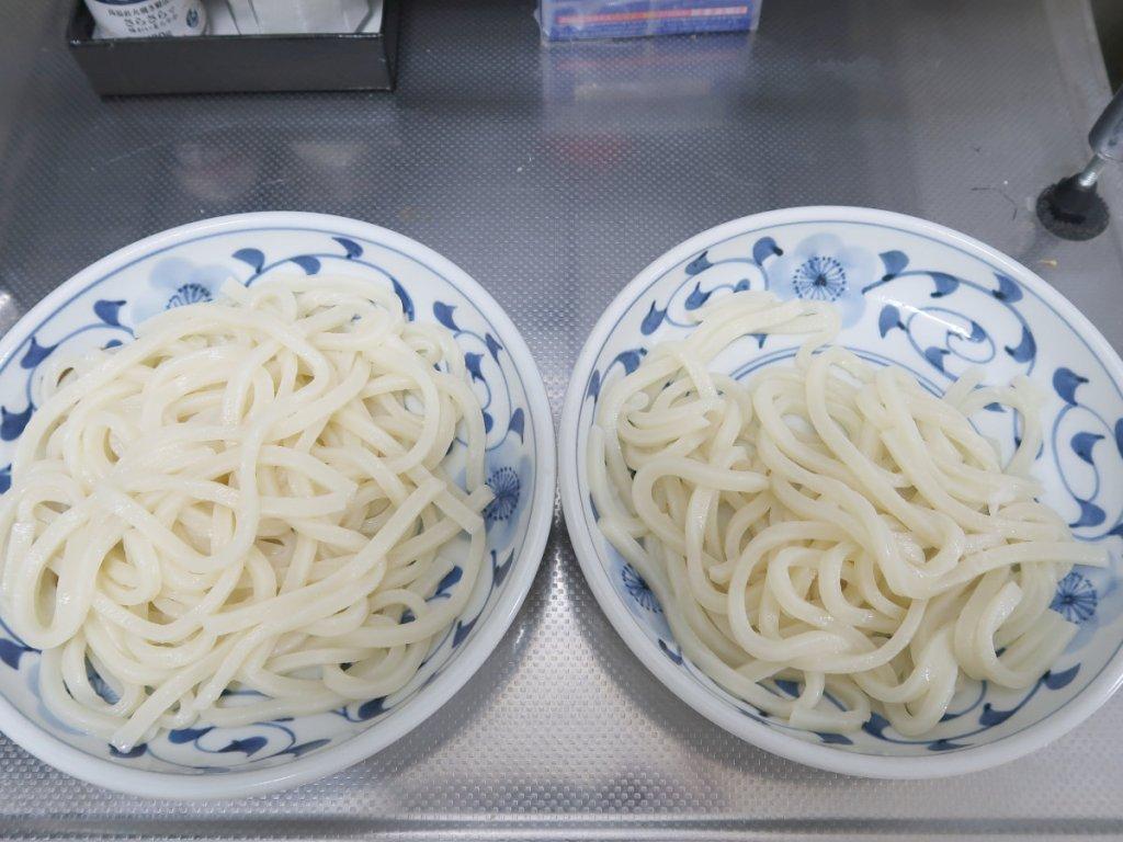 レンジで温めた冷凍うどんを皿に盛り付ける