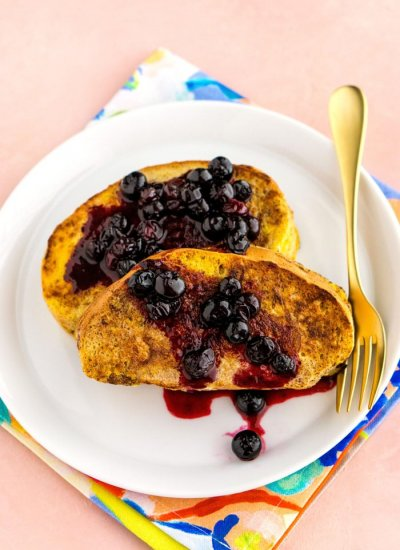 2 pieces of french toast on a while plate with blueberry sauce over the top of the toast.