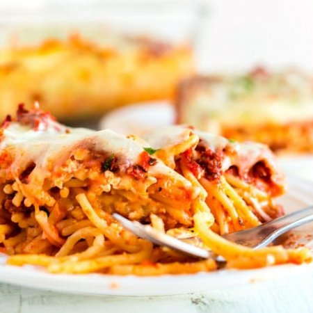 Close up picture of baked spaghetti on a white plate.