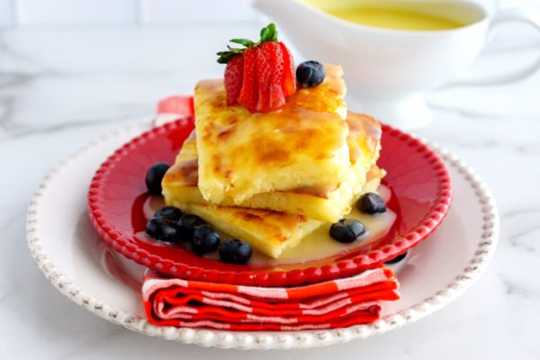 3 sheet pan pancakes stacked on top of each other with blueberries, strawberries, and buttermilk syrup.