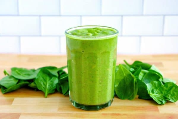 Green smoothie in a glass surrounded by Spinach.