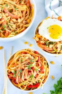 Overhead picture of Thai peanut noodles in 3 bowls and one with a fried egg on top.