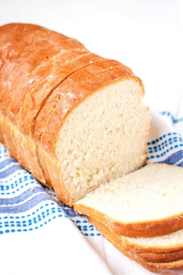 A homemade white bread loaf cut into slices.