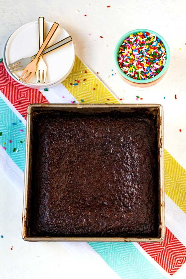 Overhead picture of a Chocolate Wacky Cake surrounded by sprinkles, white plates, and forks.