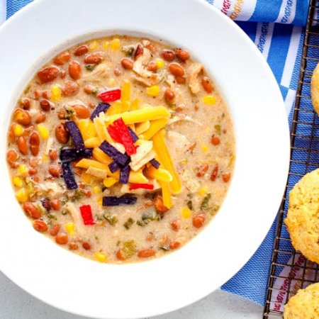 A white bowl full of crock pot white chicken chili with corn muffins.