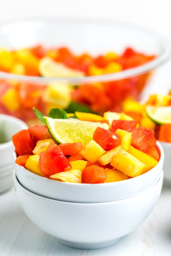 Mexican fruit salad in a white bowl with the serving bowl of fruit salad behind it.