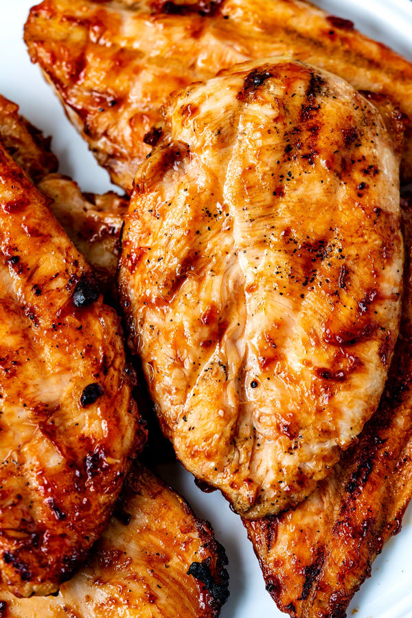 Close up picture of Grilled BBQ Chicken Breasts on a white plate.