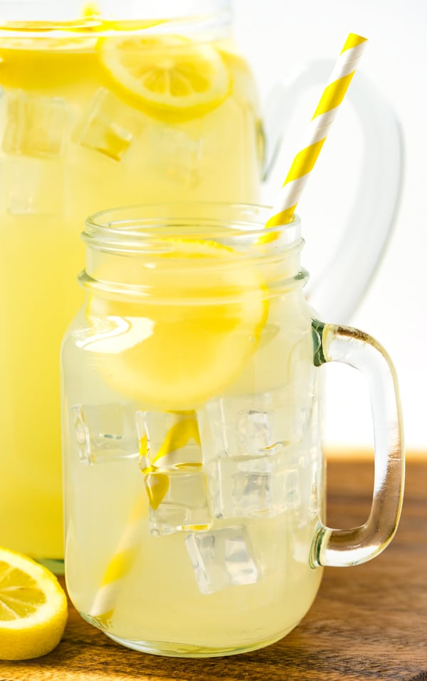 A close up picture of lemonade in a mason jar with a paper straw and a lemon slice.
