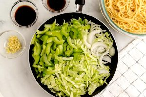 Add the veggies to the hot pan and cook until the onions are translucent and the edges of the veggies are browned.