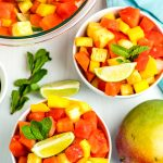 An overhead picture of Mexican fruit salad in two white bowls with lime wedges and min leaves.
