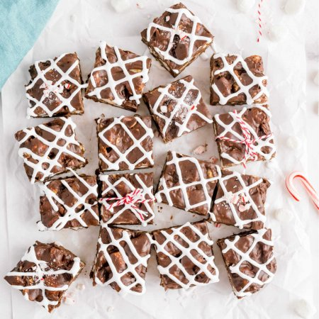 An overhead picture of sliced Christmas Rocky Road Fudge that's drizzles with marshmallow creme and crushed candy canes.