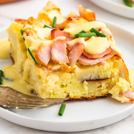 A close up picture of a slice of eggs benedict casserole on a white plate with a fork.