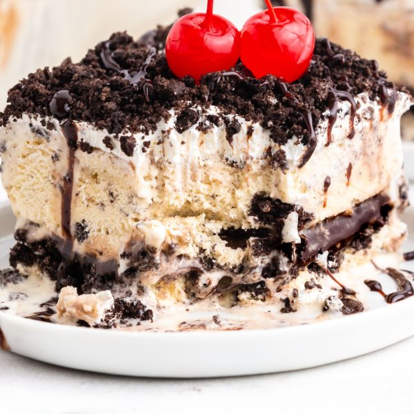 A slice of Oreo ice cream cake on a white plate topped with cherries.