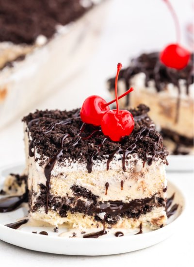 A slice of Oreo Ice Cream Cake on a white plate topped with hot fudge and cherries.