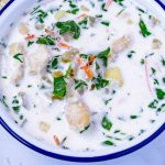 Close up picture of gnocchi soup in a white bowl.