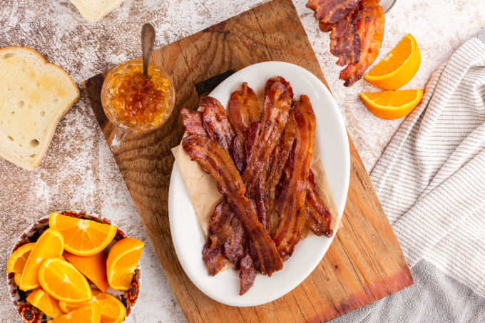 An overhead picture of candied bacon on a white serving platter with sliced oranges around it.