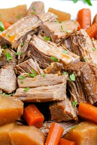 A close up picture of the finished slow cooker pot roast on a white platter.