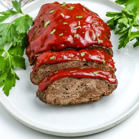 The finished instant pot meatloaf and potatoes on a white platter glazed with ketchup.