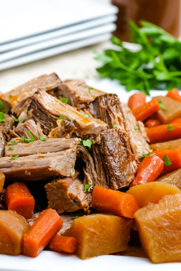 The finished slow cooker pot roast recipe served on a white platter.