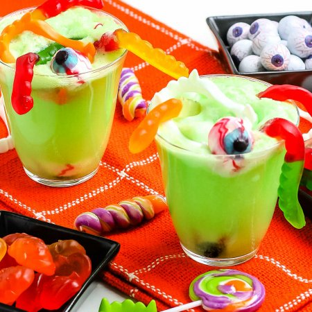 Two glasses of Witches' Brew with halloween candy in it.