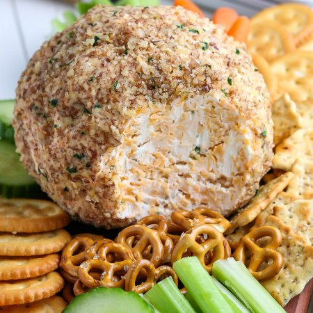 The finished classic cheese ball on a serving plate with veggies.