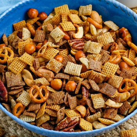 A close up picture of the finished Chex Mix in a blue bowl.