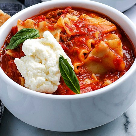 A close up picture of the finished Crockpot Lasagna Soup garnished with ricotta cheese.