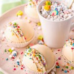 Rainbow White Hot Chocolate Bombs on a platter and in a mug.