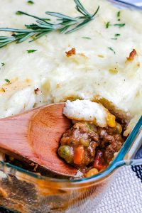A close up picture of a spoon getting a scoop of shepherd's pie.