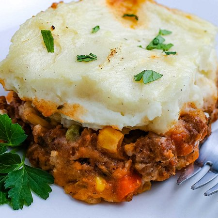 A close up picture of some Shepherd's Pie on a white plate.