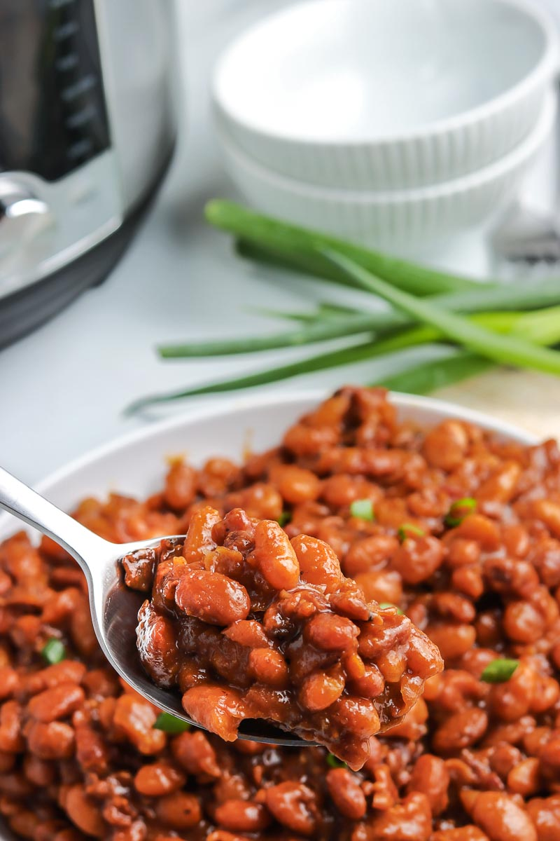 A spoon picking up some of the Instant Pot Baked Beans.