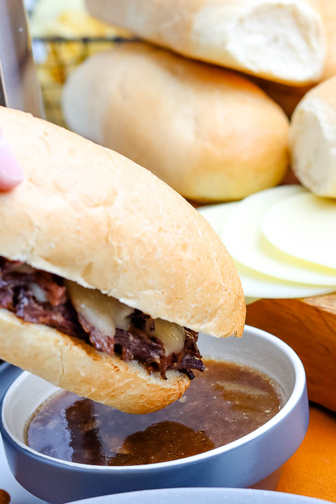 A French Dip Sandwich being dipped into au jus.