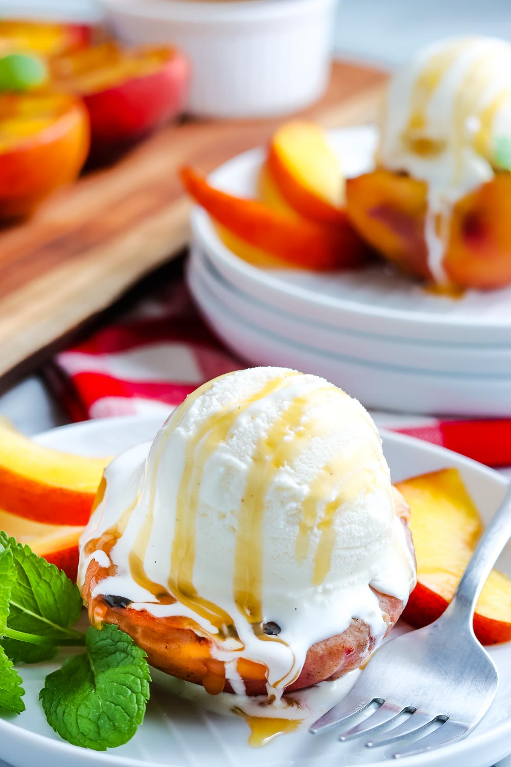 A grilled peach with a scoop of ice cream and caramel sauce.