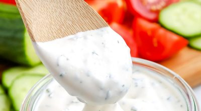 A wooden spoon dipping into Homemade Ranch Dressing.