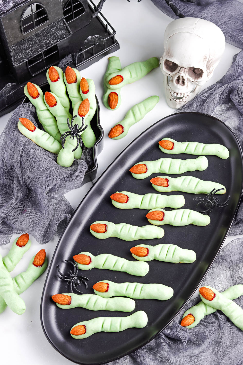 An overhead picture of Witch Finger Cookies on a black platter and in a serving bowl.