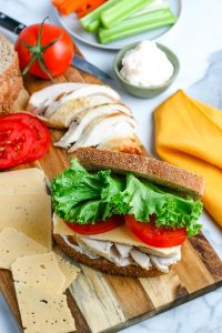 A Leftover Turkey Sandwich on a wooden cutting board.