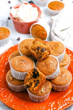 A stack of easy pumpkin muffins on an orange plate.