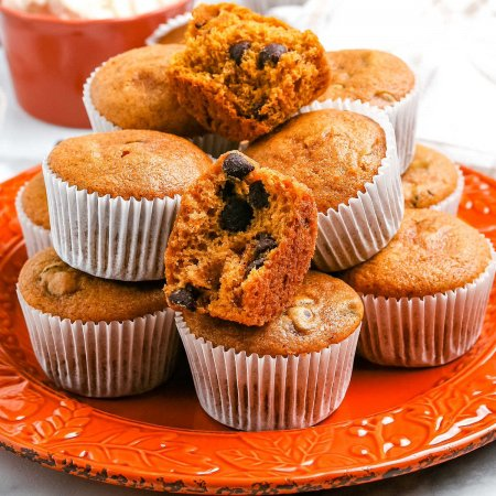 A close up picture of Pumpkin Chocolate Chip Muffins stacked on top of each other.
