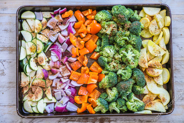 Ingredients for roasted veggies on a cookie sheet including zucchini, squash, broccoli, onion, bell pepper, and cajun seasoning.