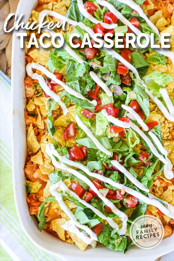 Chicken Taco Casserole in a white casserole dish garnished with lettuce, tomato, and sour cream