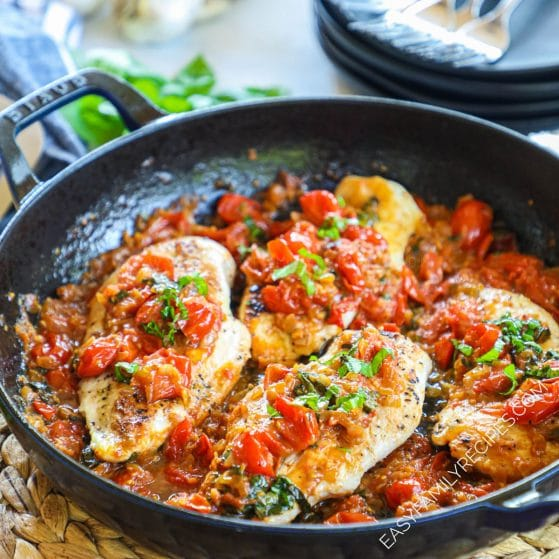 Chicken in pomodoro sauce in a skillet garnished with fresh basil.