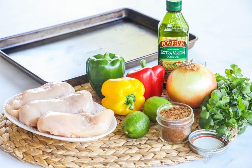 Ingredients for making baked sheet pan chicken fajitas including chicken breast, bell pepper, onion, lime, fajita seasoning, oil