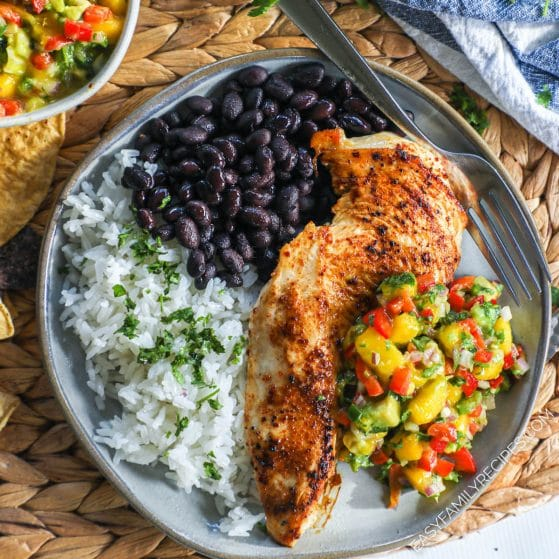 Chicken breast topped with mango salsa plated with cilantro lime rice and black beans